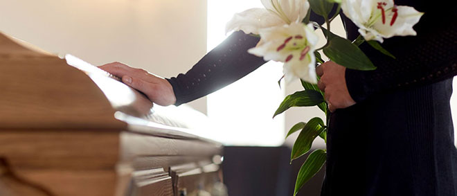 Woman at funeral casket with flowers